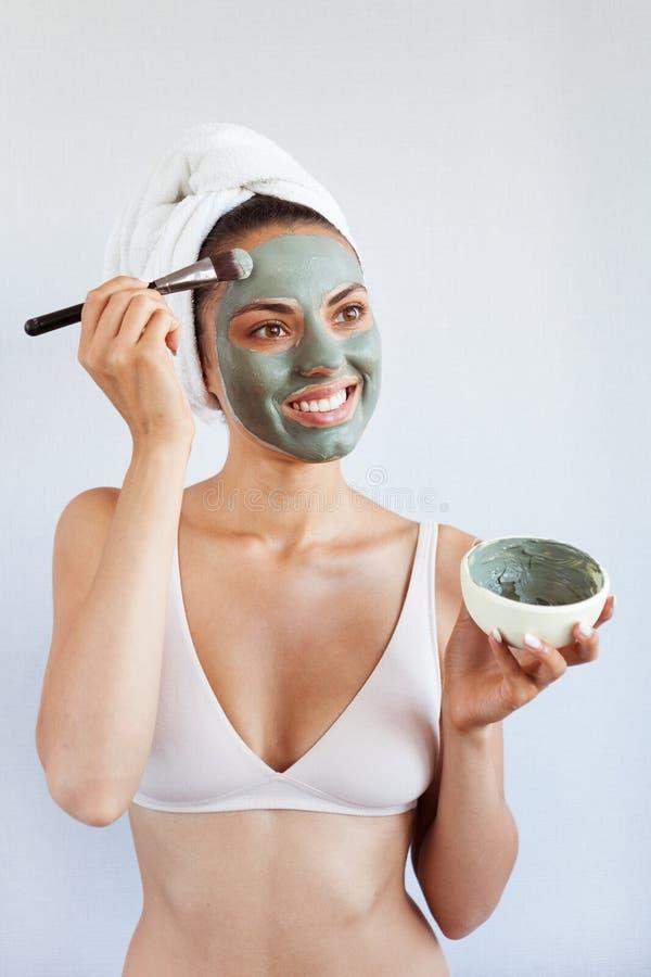 Ung härlig kvinna i framsidamaskering av terapeutisk blå gyttja Spa arkivfoton