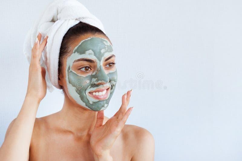 Ung härlig kvinna i framsidamaskering av terapeutisk blå gyttja Spa royaltyfri foto
