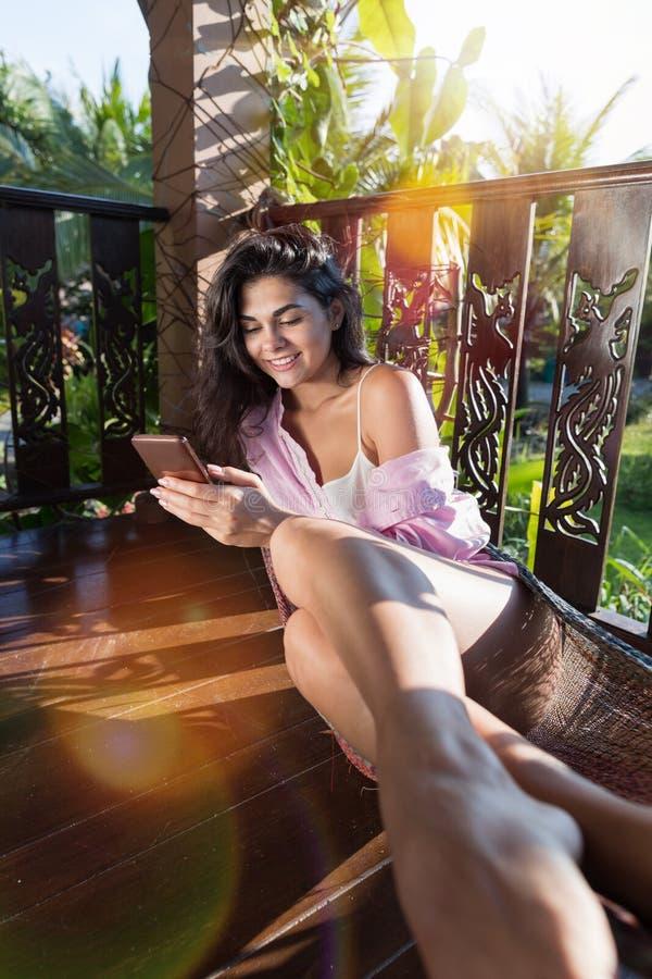 Ung härlig kvinna i hängmatta på för Smart för cell för sommarterrassbruk koppla av för flicka telefon lyckligt le attraktivt royaltyfria bilder