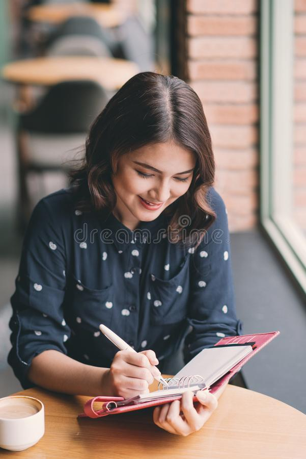 Ung härlig kvinna i kafét nära fönstret som tänker och skriver något royaltyfri fotografi