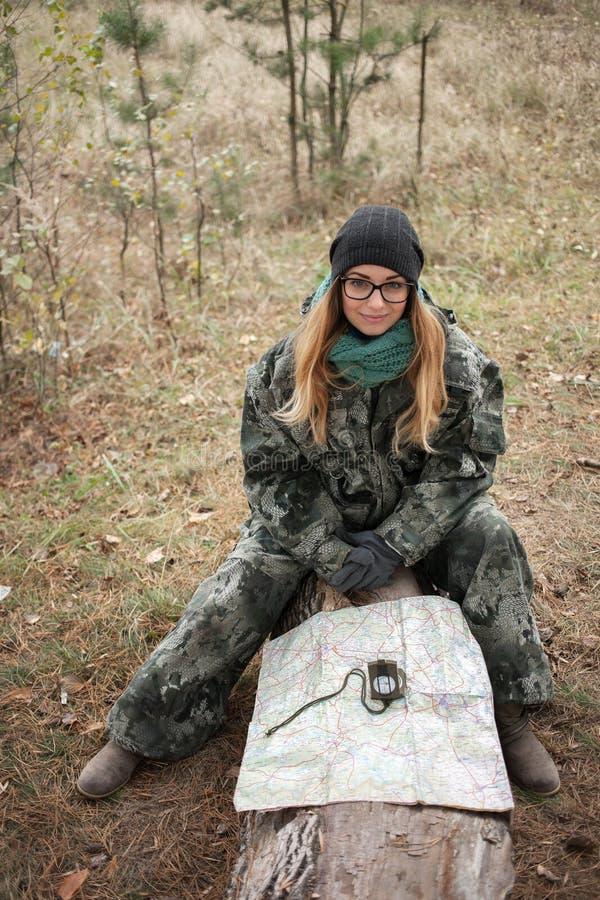 Ung härlig kvinna i kamouflagedräktsammanträde på skogjournalen som upptäcker naturen i skogen med kompasset och översikten Loppl arkivfoton