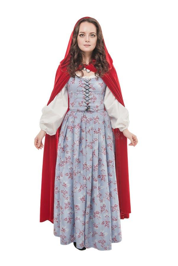 Ung härlig kvinna i lång medeltida klänning och röd kappa royaltyfri bild