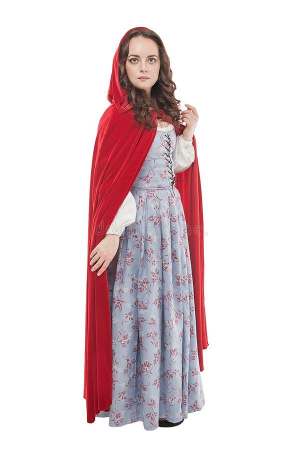 Ung härlig kvinna i lång medeltida klänning och röd kappa royaltyfri fotografi