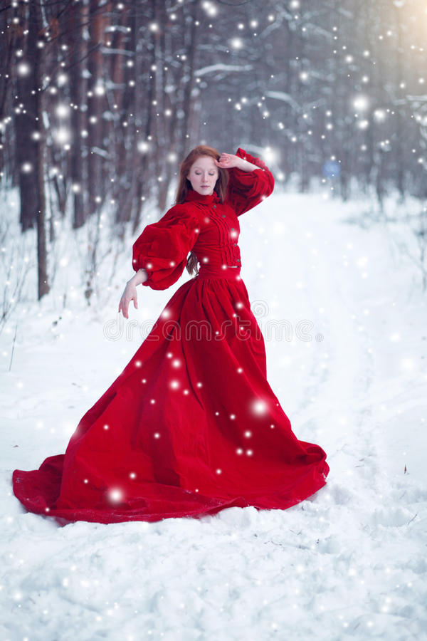Ung härlig kvinna i lång röd klänning över vinterbakgrund arkivbild