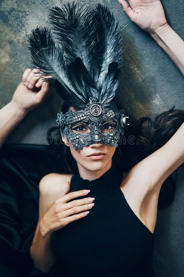 Ung härlig kvinna i maskeradkarnevalmaskeringen som ligger på golv royaltyfria bilder