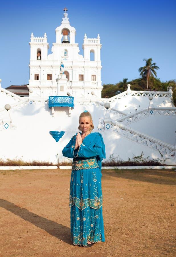Ung härlig kvinna i nationell indierkläder nära den katolska templet, Goa arkivfoto