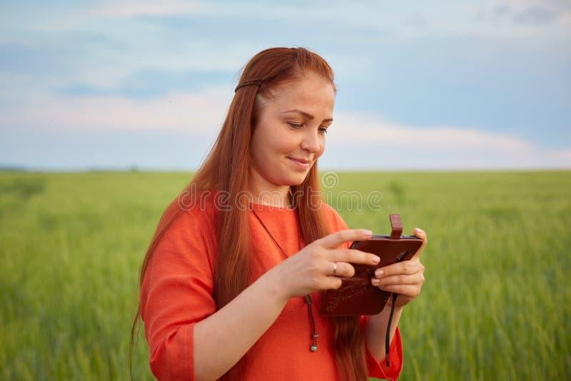 Ung härlig kvinna i röd klänning med rött hår håll ögonen på dina foto på din telefon och ställningar i ett grönt vetefält in arkivfoto