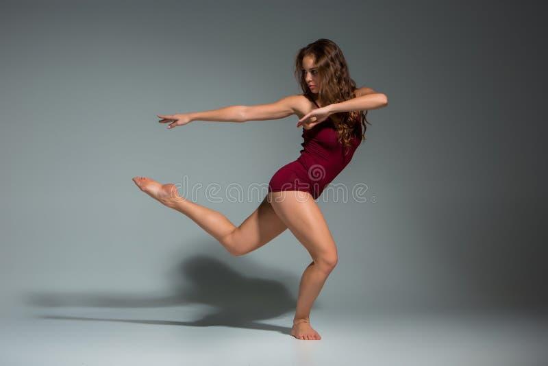 Ung härlig kvinna i röd T-tröja och kortslutningar som dansar på ett mörker - grå studiobakgrund arkivbild