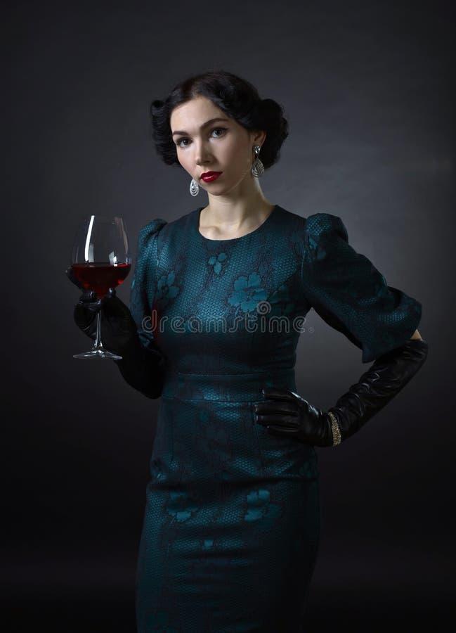 Ung härlig kvinna i retro stil med rött vin royaltyfri fotografi