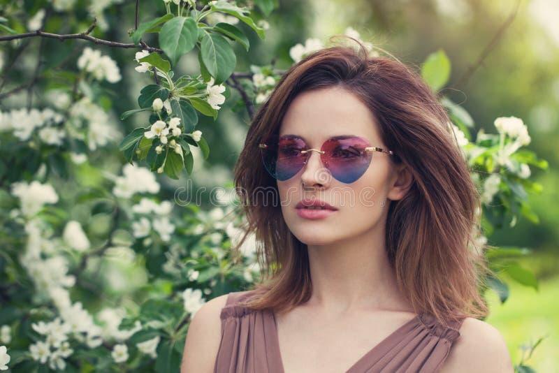 Ung härlig kvinna i solglasögon utomhus Gullig flicka med brunt i lager hår, vårstående royaltyfri bild