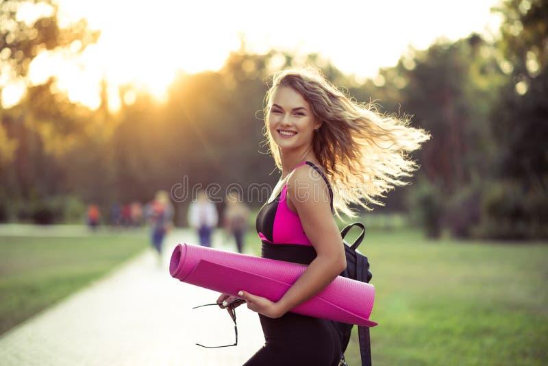 Ung härlig kvinna i sportswear Henne ` s som rymmer en utbildning matt Gå att göra sportar som utbildar, gymnastik utomhus royaltyfri fotografi