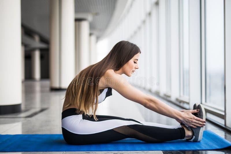 Ung härlig kvinna i sportswearen som gör sträckning, medan sitta på golvet framme av fönstret på idrottshallen arkivfoton