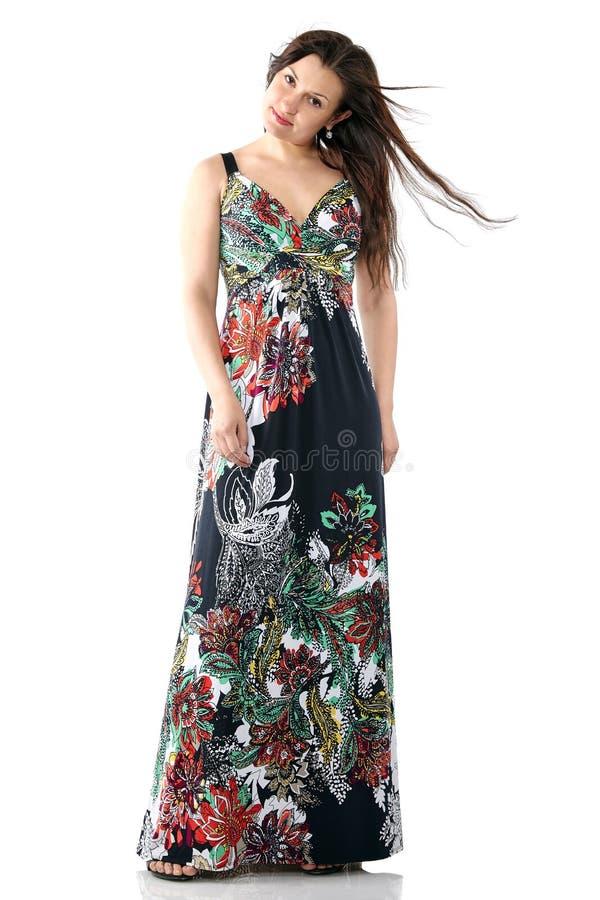 Ung härlig kvinna i sundress med den färgrika blommamodellen, långt hår, full kroppstående fotografering för bildbyråer
