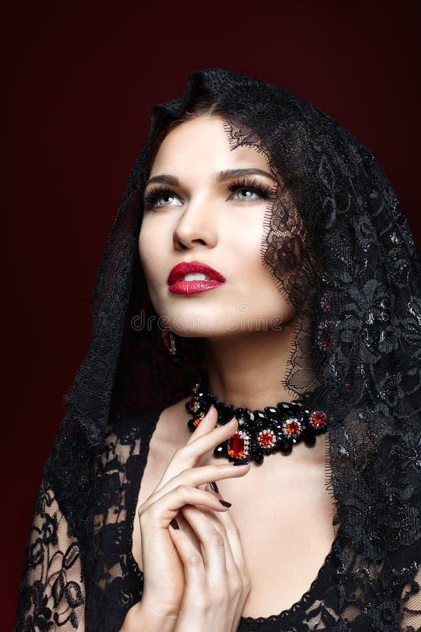 Ung härlig kvinna i svart klänning på marsalafärgbakgrund royaltyfri foto