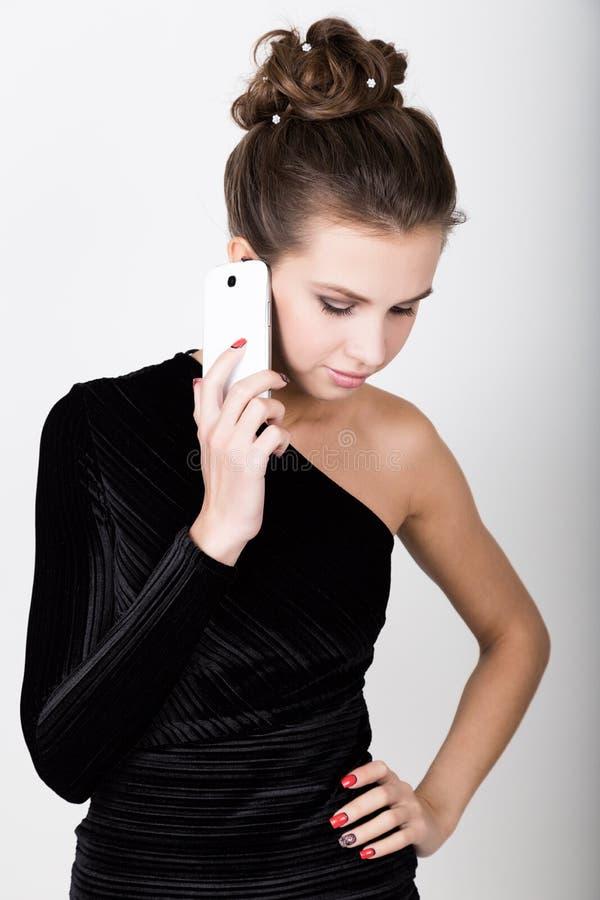 Ung härlig kvinna i svart klänning som talar till din mobiltelefon royaltyfri fotografi