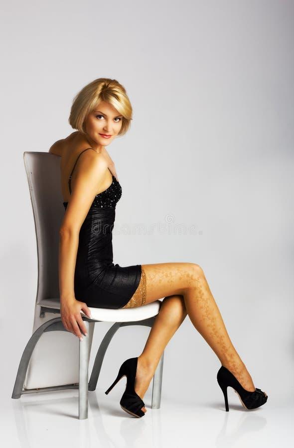 Ung härlig kvinna i svart klänningsammanträde på en stol arkivfoton
