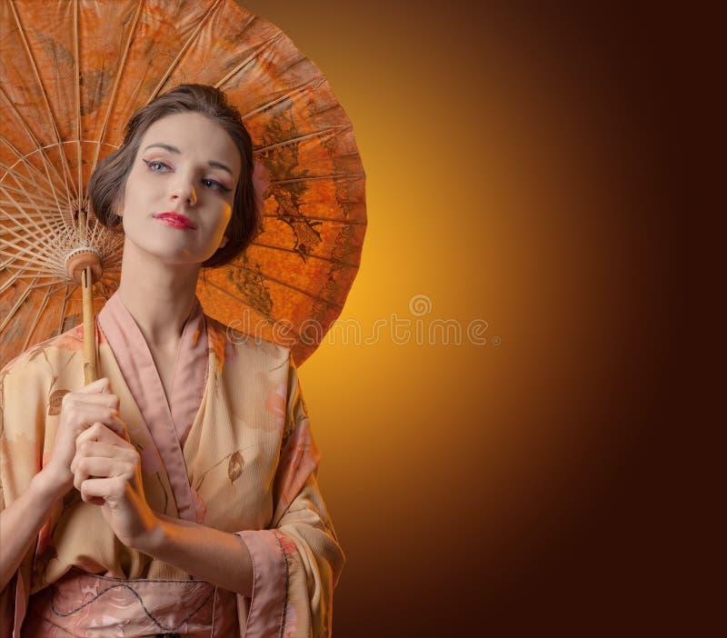 Ung härlig kvinna i traditionell japansk kimono med umbrel royaltyfri foto
