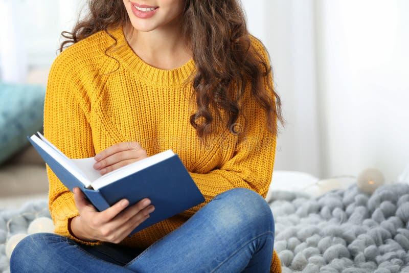 Ung härlig kvinna i varm tröjaläsebok royaltyfri foto