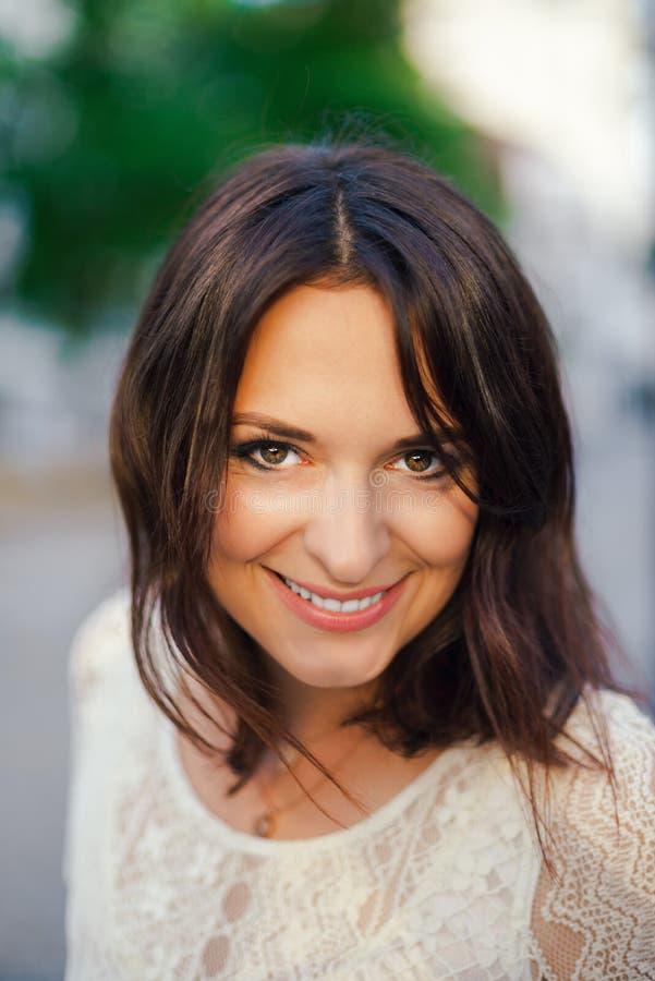 Ung härlig kvinna, mörker-haired och att le och att plira in i ramen som besöker centret på en solig dag, i en vit klänning för royaltyfria foton