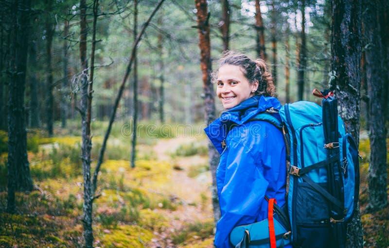 Ung härlig kvinna med att fotvandra ryggsäcken i skogen som tycker om naturen och ensamhet royaltyfria foton