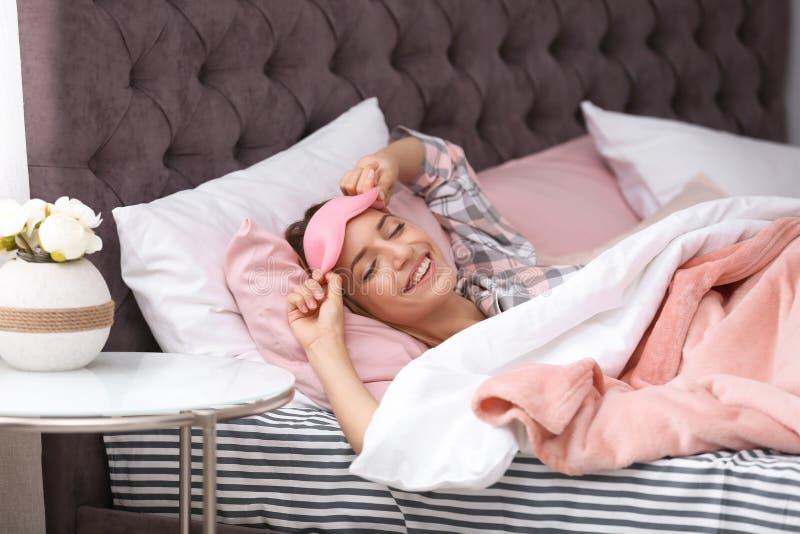 Ung härlig kvinna med att sova maskeringen som vaknar upp royaltyfri bild