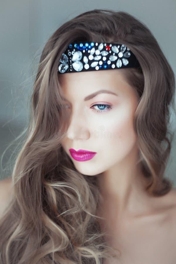 Ung härlig kvinna med beslaget i hår och blåa ögon arkivbild