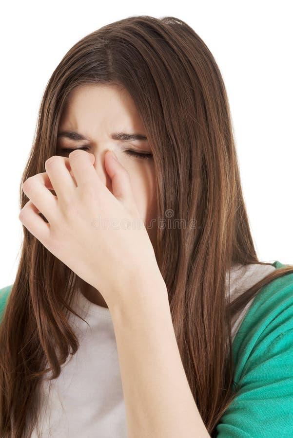 Ung härlig kvinna med bihålatryck som trycker på hennes näsa. royaltyfria bilder