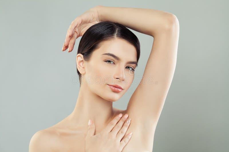 Ung h?rlig kvinna med den sunda handen f?r hudst?endeinnehav upp och visa armh?lor arkivbilder