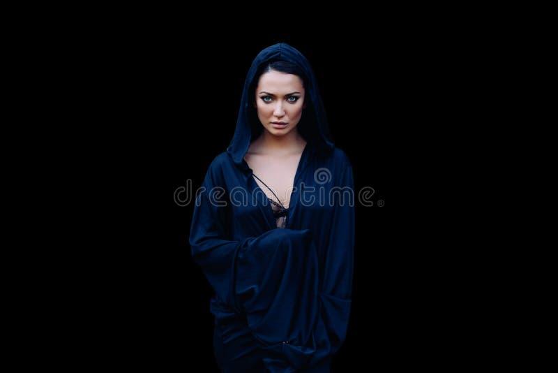 Ung härlig kvinna med ett svart hår och i det mörkt - blå kappa med huven på den svarta bakgrunden royaltyfria foton