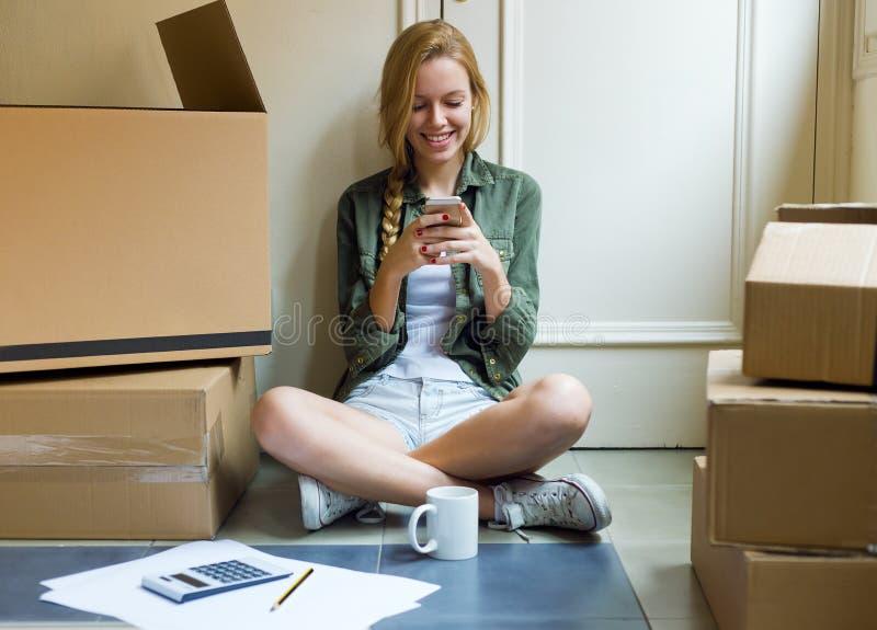 Ung härlig kvinna med mobiltelefonen i hennes nya hus royaltyfria bilder
