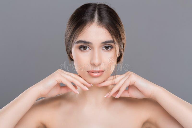Ung härlig kvinna med perfekt hud som masserar hennes framsida royaltyfri fotografi