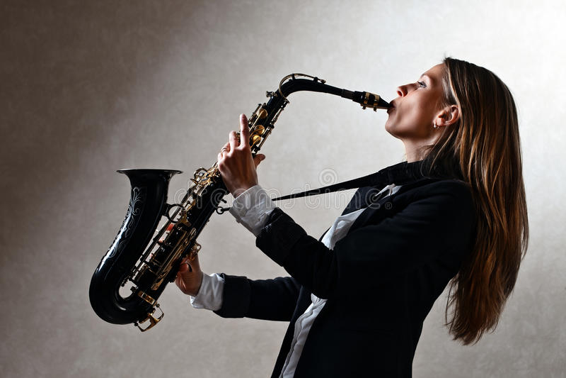 Ung härlig kvinna med saxofonen royaltyfria foton