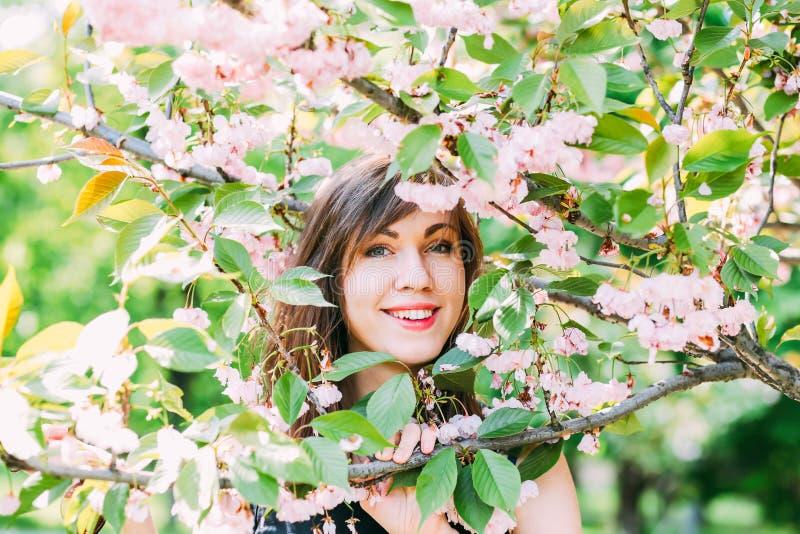 Ung härlig kvinna nära sakura det blommande trädet Rosa färgblommor, vår och ungdombegrepp stilfull flicka royaltyfri bild