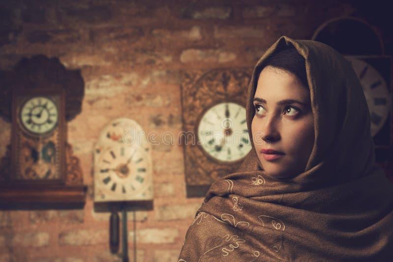 Ung härlig kvinna och klockor på den gamla väggen fotografering för bildbyråer