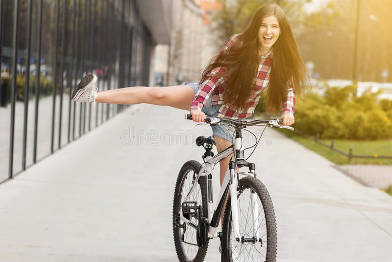 Ung härlig kvinna på en cykel arkivfoton