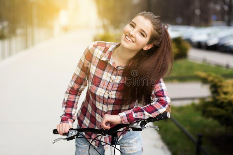 Ung härlig kvinna på en cykel arkivfoto