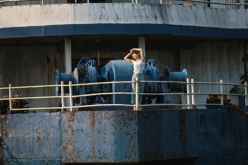 Ung härlig kvinna på ett övergett jätte- metallskepp arkivfoto