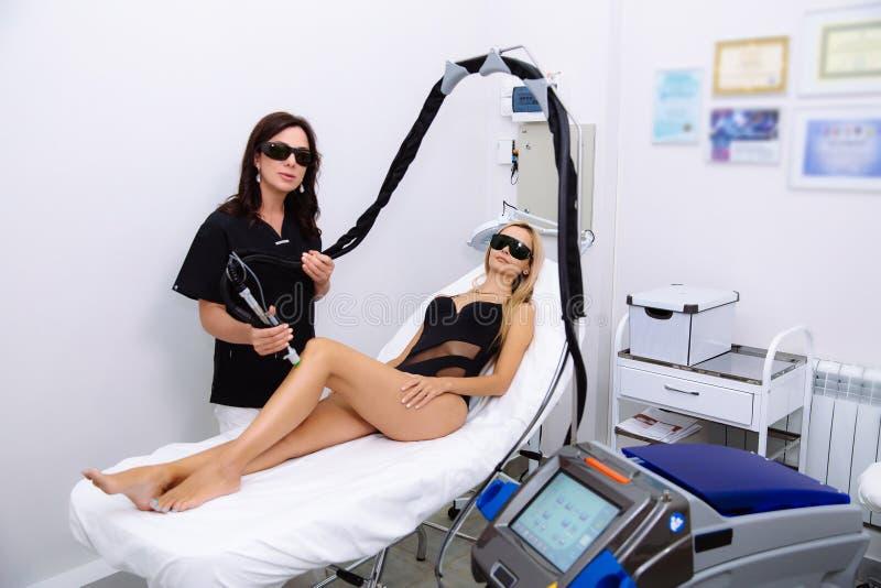 Ung härlig kvinna på tillvägagångssätt för laser-hårborttagning i kosmetologs kontor arkivfoton