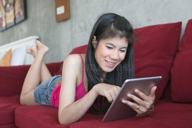 Ung härlig kvinna som använder datorminnestavlan på den röda soffan royaltyfria bilder