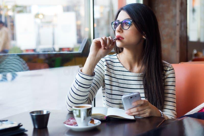 Ung härlig kvinna som använder hennes mobiltelefon i kaffe royaltyfri foto