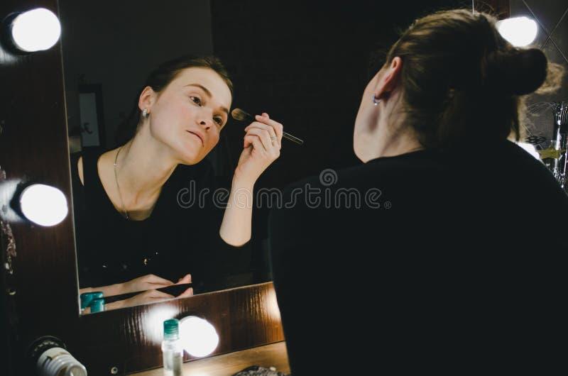 Ung härlig kvinna som applicerar hennes sminkframsida med borsten och att se i en spegel som sitter på stol på loge med royaltyfria foton