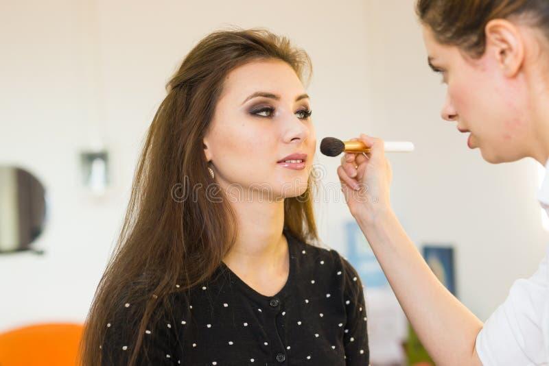 Ung härlig kvinna som applicerar smink av sminkkonstnären fotografering för bildbyråer