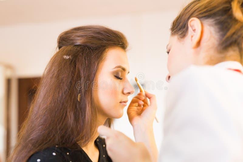 Ung härlig kvinna som applicerar smink av sminkkonstnären royaltyfri foto