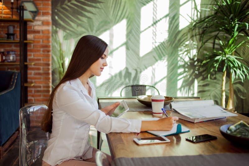 Ung härlig kvinna som arbetar i ett stilfullt kontor i vindstil fotografering för bildbyråer