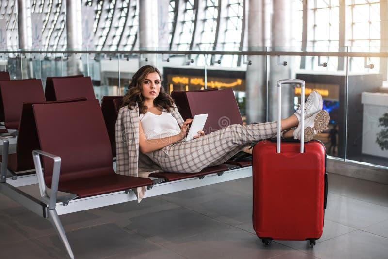 Ung härlig kvinna som arbetar med den digitala minnestavlan i väntande rum för flygplats arkivfoto