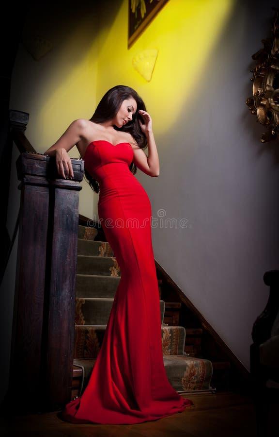 Ung härlig kvinna som bär en röd klänning i det gamla hotellet fotografering för bildbyråer