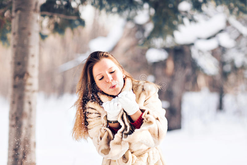Ung härlig kvinna som blåser insnöad vinter arkivbild