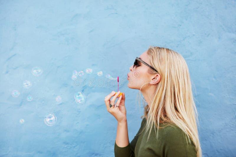Ung härlig kvinna som blåser såpbubblor royaltyfria foton
