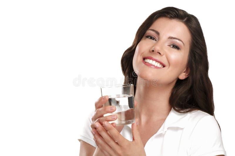 Ung härlig kvinna som dricker ett exponeringsglas av vatten arkivbild