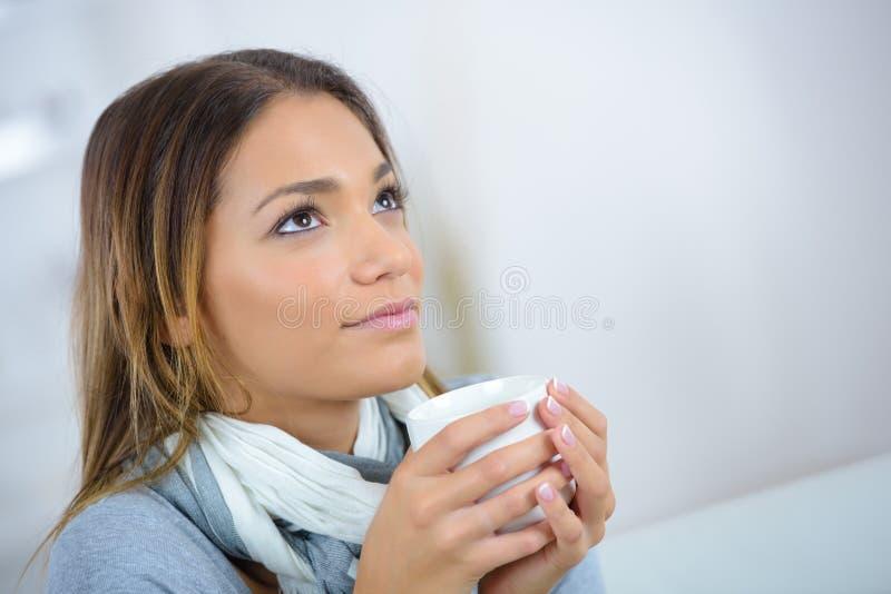 Ung härlig kvinna som dricker kaffe eller te och tänka royaltyfri bild